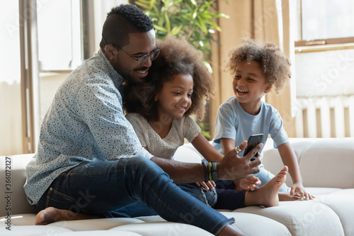 Valokuvatapetti Overjoyed young african American father with little kids have fun watching funny