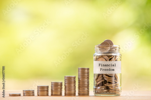 Obraz A glass jar filled with coins placed beside a pile of coins. Saving money for financial independence or financial freedom concept. - fototapety do salonu