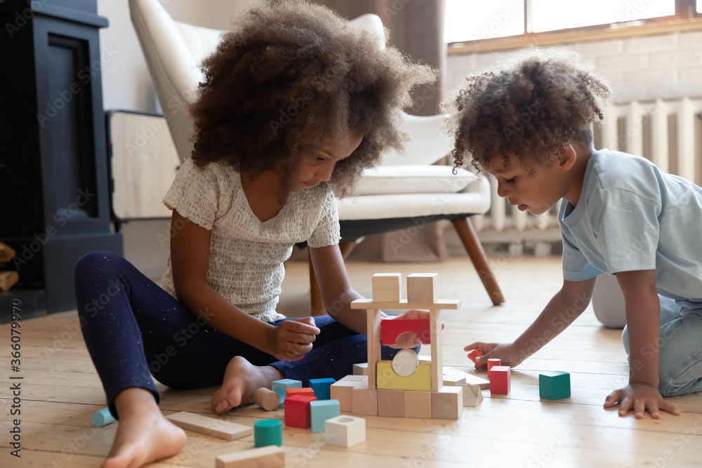 Fototapeta Playful little biracial kids siblings sit on warm floor at home build play with wooden bricks together, small african American brother and sister children construct with blocks cubes in living room