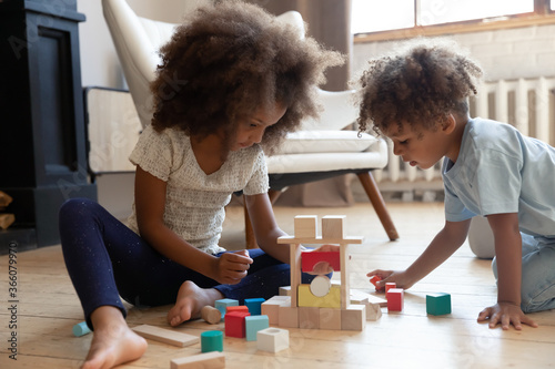 Photo Playful little biracial kids siblings sit on warm floor at home build play with