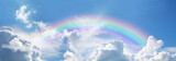 Fototapeta Rainbow - Stunning blue sky panoramic rainbow - big fluffy clouds with a giant arcing rainbow against a  beautiful summer time blue sky with copy space for messages
