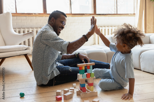 Cuadros en Lienzo Happy young african American father and little ethnic son give high five playing