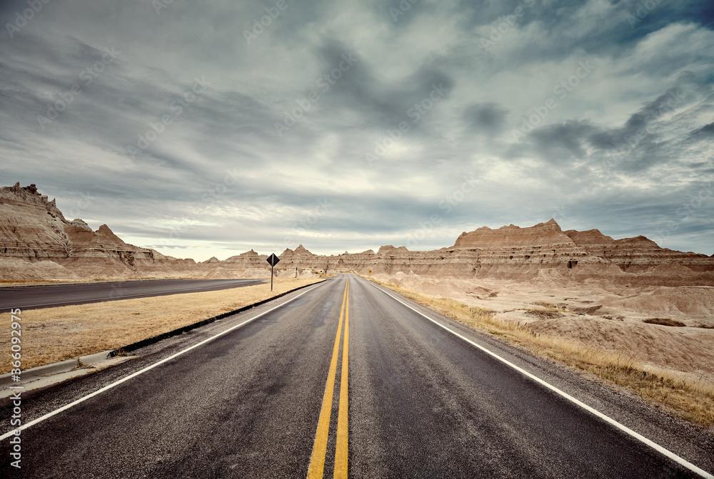 Fototapeta Scenic road in Badlands National Park, color toning applied, travel concept, USA.