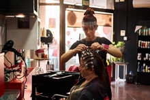 Hairdresser Combs A Client Wit...