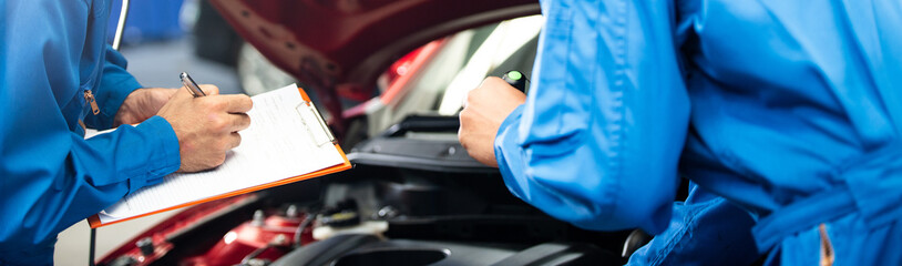 Banner of automotive mechanic men with assistant checking damage under-car condition, vehicle maintenance technician write on checklist document in garage at auto repair shop. after service concept