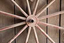 Wagon Wheel Against A Wooden W...