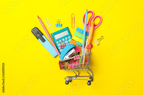 Fototapeta Shopping trolley with school supplies on yellow background, space for text obraz