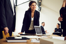 Smiling Female Professional Looking At Colleagues During Meeting In Law Firm