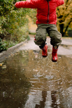 Boy Jumping In Puddle On Road