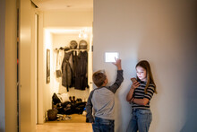 Girl Text Messaging On Smart Phone While Brother Using Digital Tablet Mounted On Wall At Modern Home