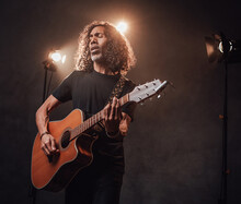 Middle Aged Hispanic Musician In Black T-shirt Emotionally Singing And Playing Guitar. View Of Musician In The Spotlight