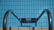 Pattern Of Water Of Swimming Pool With Light In It And Pool's Stairway, A Lot Of Space For Text Over Blue Water With Play Of Light And Shadow On Pools Bottom. Detail Of Beautiful Swimming Pool.