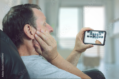 The man gets acquainted with the details of the upcoming dental treatment through a telemedicine application Canvas Print