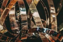 Aged Dirty Movie Film Rolls, Retro Reels, Filmstrip, Photographic Film, Shallow Depth Of Field. Vintage Background, Retro Style. Photo, Movie, Cinema Concept