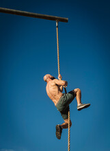 Man Climbing On Rope