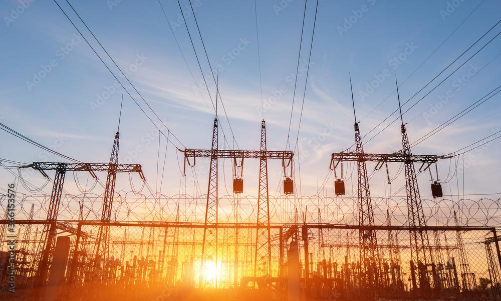 Fototapeta High-voltage power lines at sunset or sunrise. High voltage electric transmission tower