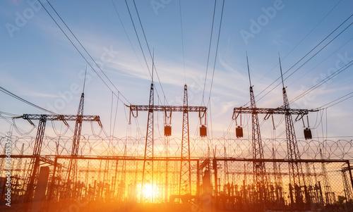Fototapeta High-voltage power lines at sunset or sunrise. High voltage electric transmission tower obraz