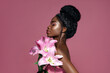 canvas print picture - Profile portrait of young beautiful African American model posing with lily flowers against pink background