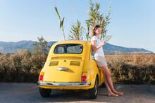 Woman Leaning At Yellow Vinage Car Looking At Map, Sardinia, Italy