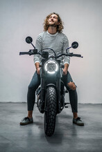 Young Man Looking Up Sitting On Motorcycle
