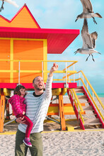 Happy Father Carrying Daughter Feeding Seagulls While Standing At Miami Beach, Florida, USA