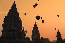 Indonesia, Java Island, Silhouettes Of Hot Air Balloons Flying Over Prambanan Temple At Moody Dusk