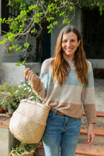 Smiling Woman Carrying Wicker Basket While Standing Against Farmhouse