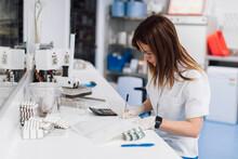 Confident Female Scientist Wri...