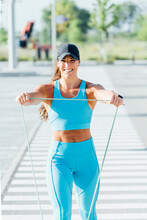 Portrait Of Smiling Young Woman Exercising With Resistance Band On Sunny Day