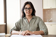 Smiling young indian female teacher wearing glasses sitting at table. Indian woman school tutor or university student studying working from home office giving online remote classes concept. Portrait