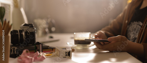Photo Female photographer holding smartphone while sitting at worktable with camera an