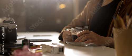 Photo Female photographer holding coffee cup while sitting at worktable with camera an