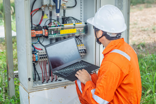 Obraz Engineers upload data of power energy to a laptop for checking the performance of the solar panel to confirming systems working normally. Concepts professional engineer for the Solar cell power plant - fototapety do salonu