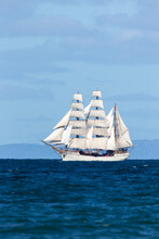 Historic Clipper Sailing Ship On Open Blue Water In Full Sail.