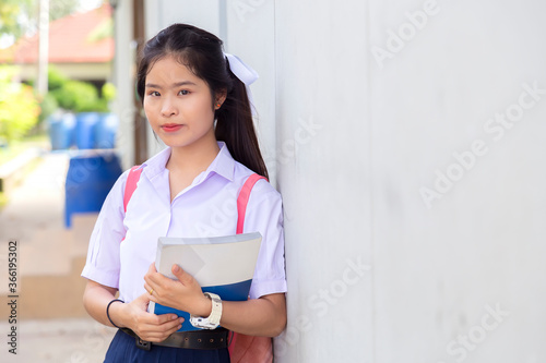 Photo Thai student holding a book on a white background Cute schoolgirl smiles and holds books in hand ready to attend school