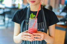Attractive Young Woman Waiter Holding Red Colorful Refreshing Cocktail With Ice And Lime. Fruit Tropical Mix Drink.