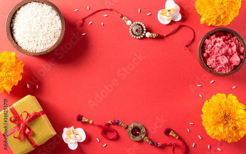 Raksha Bandhan, Indian festival with beautiful Rakhi and  Rice Grains on red background фототапет