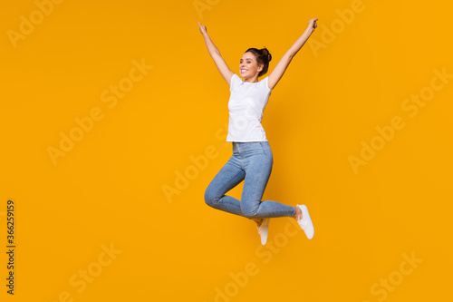 Obraz Full length body size view of her she nice-looking attractive lovely cheerful cheery girl jumping rising hands up rejoicing isolated over bright vivid shine vibrant yellow color background - fototapety do salonu