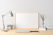 Horizontal poster frame mockup on the wooden table of home studio workspace with white wall. Front view, clipping path around poster picture.