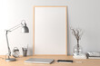 Vertical poster frame mockup on the wooden table of home studio workspace with white wall. Front view, clipping path around poster picture.