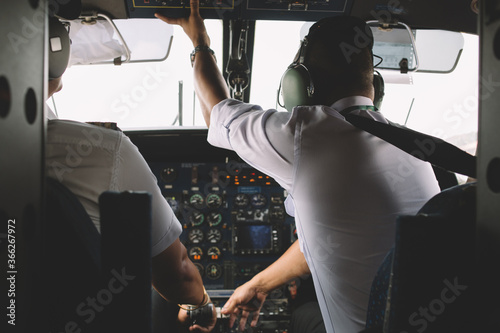 Valokuva Rear view of two professional pilots dressed in white uniform sitting in private cabin of the plane to control cockpit engine of airplane in air