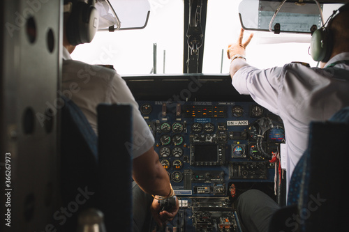 Back view of two men: pilot and copilot sitting at control cockpit panel in cabin of modern airplane Canvas-taulu
