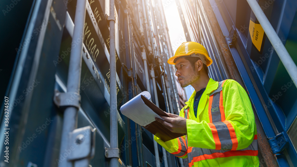 Fototapeta Smart Engineer or supervisor checking and control loading Containers box from Cargo at harbor.Foreman control Industrial Container Cargo freight ship at industry.Transportation and logistic concept.