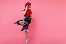 Excited Brunette Lady In Black Skirt Dancing On Rosy Background. Appealing White Girl In French Beret Jumping In Studio.
