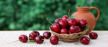 Large Red Cherries In A Basket And A Jug Of Milk Isolated On Green.