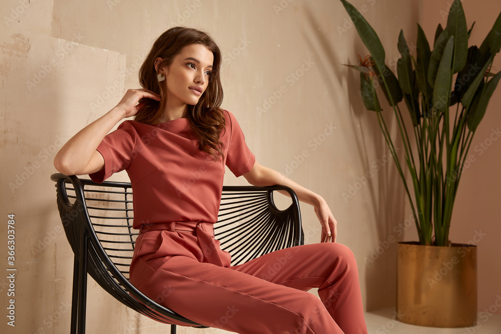 Fototapeta Beautiful brunette woman natural makeup wear fashion clothes casual dress code office style total pink blouse and pants suit, romantic date business meeting armchair interior stairs flowerpot.