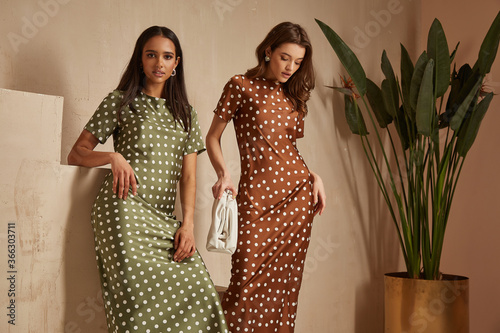 Two fashion model brunette hair wear green brown dots silk dress sandals accessory clothes date party walk interior journey summer collection plant flowerpot stairs beautiful woman tan skin friends.