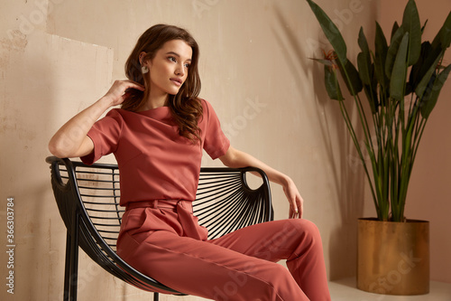 Beautiful brunette woman natural makeup wear fashion clothes casual dress code office style total pink blouse and pants suit, romantic date business meeting armchair interior stairs flowerpot.