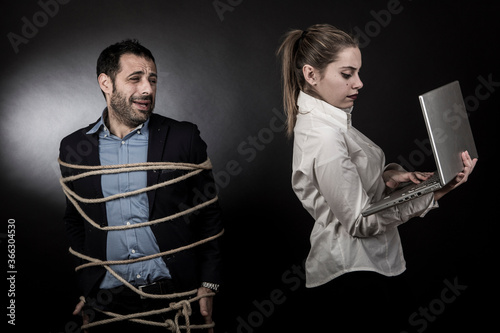 Photo uomo moro in giacca scura e camicia blu, legato con una corda, è disperato vicin