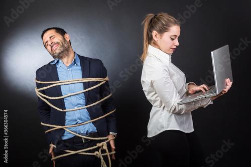 uomo moro in giacca scura e camicia blu, legato con una corda, è disperato vicin Canvas Print